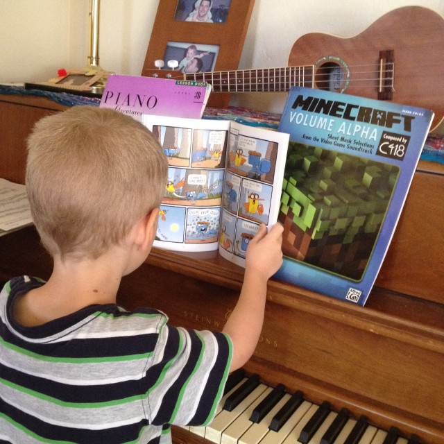 reading comics at the piano