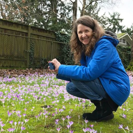 Me in my blue coat crouching in a field of crocuses, grinning at my husband who is taking a picture of me taking a picture
