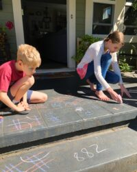 Huck and Rilla doing math with chalk on the front porch
