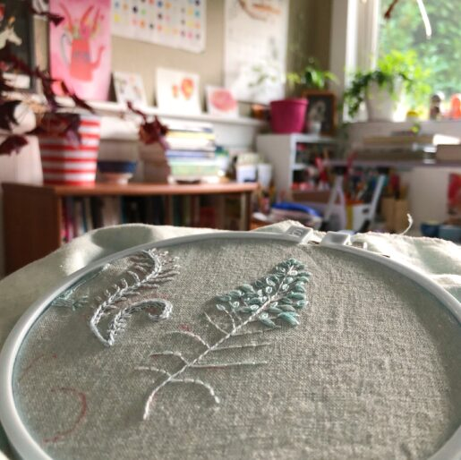 Photo of an embroidery hoop with a fern half stitched