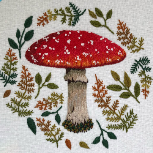 an embroidered mushroom surrounded by autumn leaves